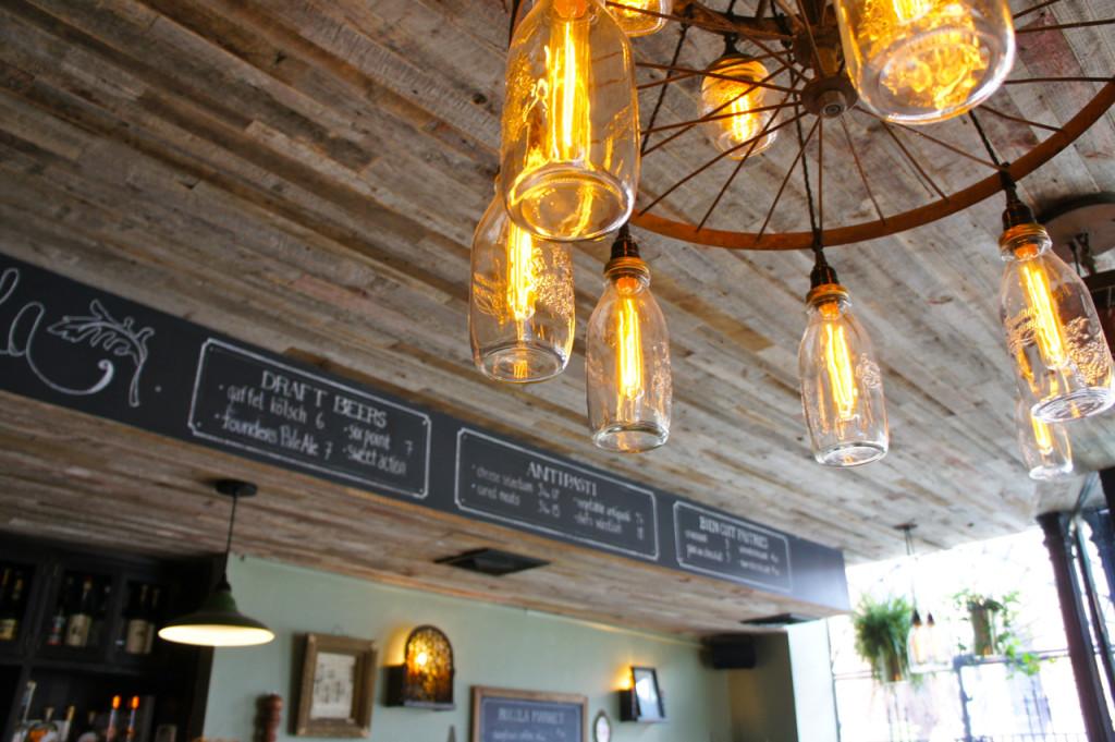 O teto com madeira rústica e as luzes com garrafas antigas de leite e geléia.