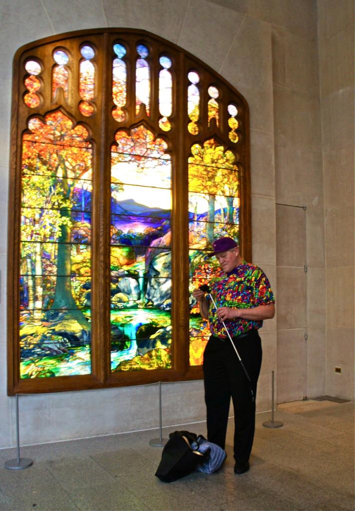 """Um aficionado do vitrais da Tiffany.  Olhem só a camisa dele!  E ele fazia filmes dele mesmo na frente desta janela com a sua câmera que estava neste """"braço"""" longo."""
