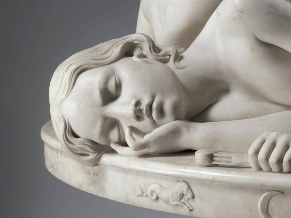 """Ela está sonhando com a realização de seus planos ou planejando a realização de seus sonhos? Não se iludam: no Domus (10ª Casa) das cabras não se dorme em serviço. Trecho da escultura """"La Table aux Amours"""" ou """"The Demidoff Table"""" (1845), do italiano Lorenzo Bartolini (1777–1850), que está no Museu Metropolitano de Arte, em Nova Iorque."""