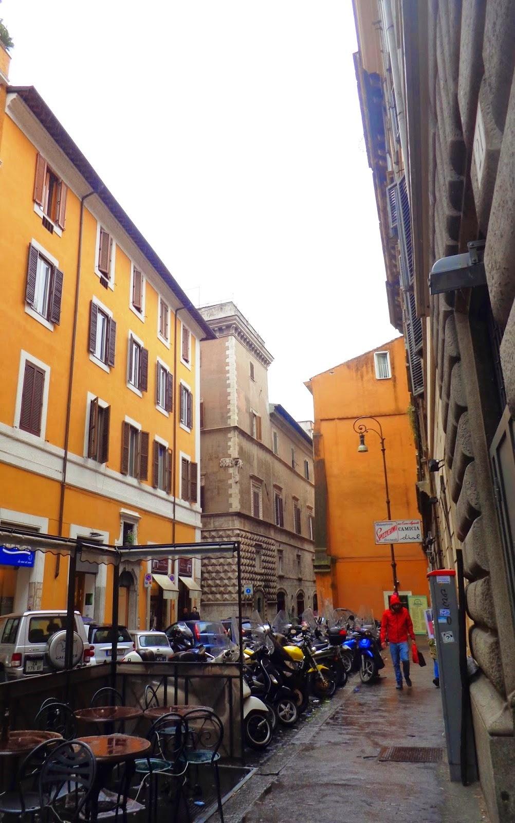 Ao fundo, parte do Palazzo Santacroce, que é uma construção única em seu gênero. Seu aspecto geral remete a uma fortaleza medieval, evidenciando a intenção de seu arquiteto. A quina do Palazzo projeta-se atualmente de maneira impositiva sobre a rua.