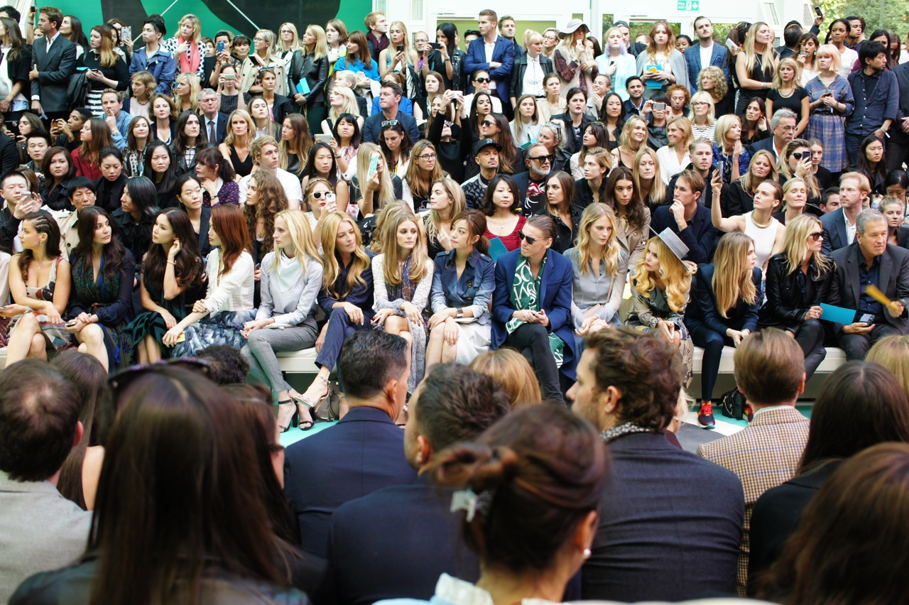 Entre as Vips da primeira fila Kate Moss e Cara Delevingne com Mario Testino e no meio Olivia Palermo: