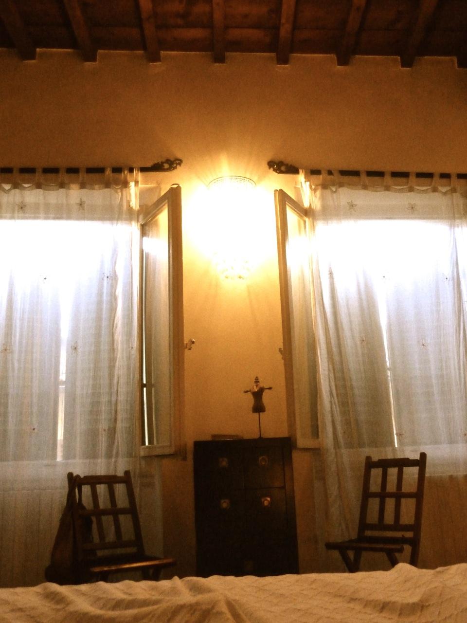 Um detalhe do quarto com 2 janelas (que davam para a rua e, por isso, era meio barulhento) e as vigas de madeira no teto.