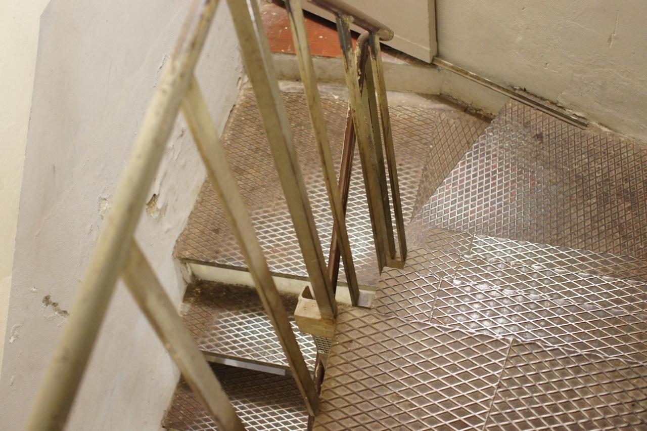 As escadas de ferro industriais que levam ao primeiro andar onde se esconde o restaurante.
