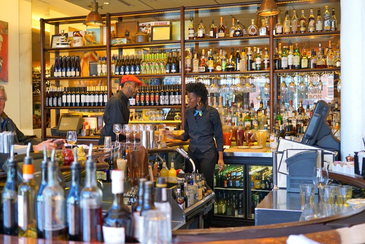 O espaço é elegante e informal com muito charme e personalidade.  Entra-se e se vê o bar.  Atrás da parede de copos e garrafas está o restaurante.