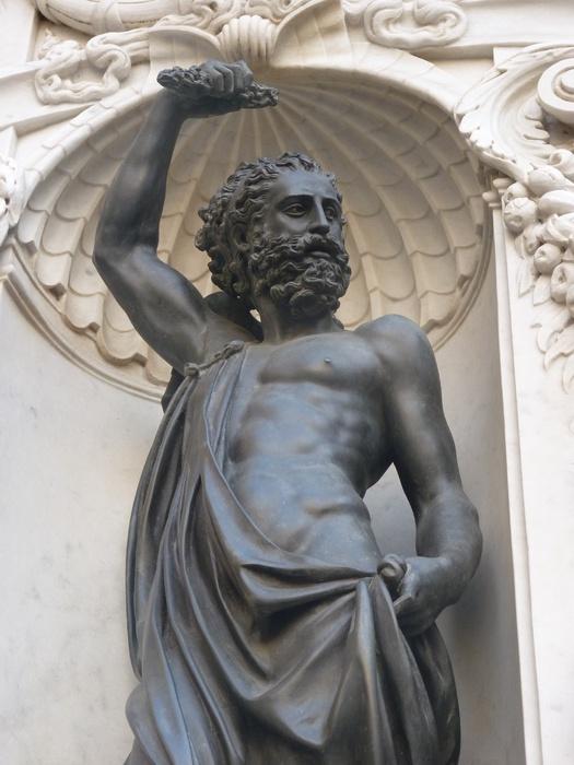 Zeus (Júpiter) tem seu braço direito erguido, onde segura seu raio.