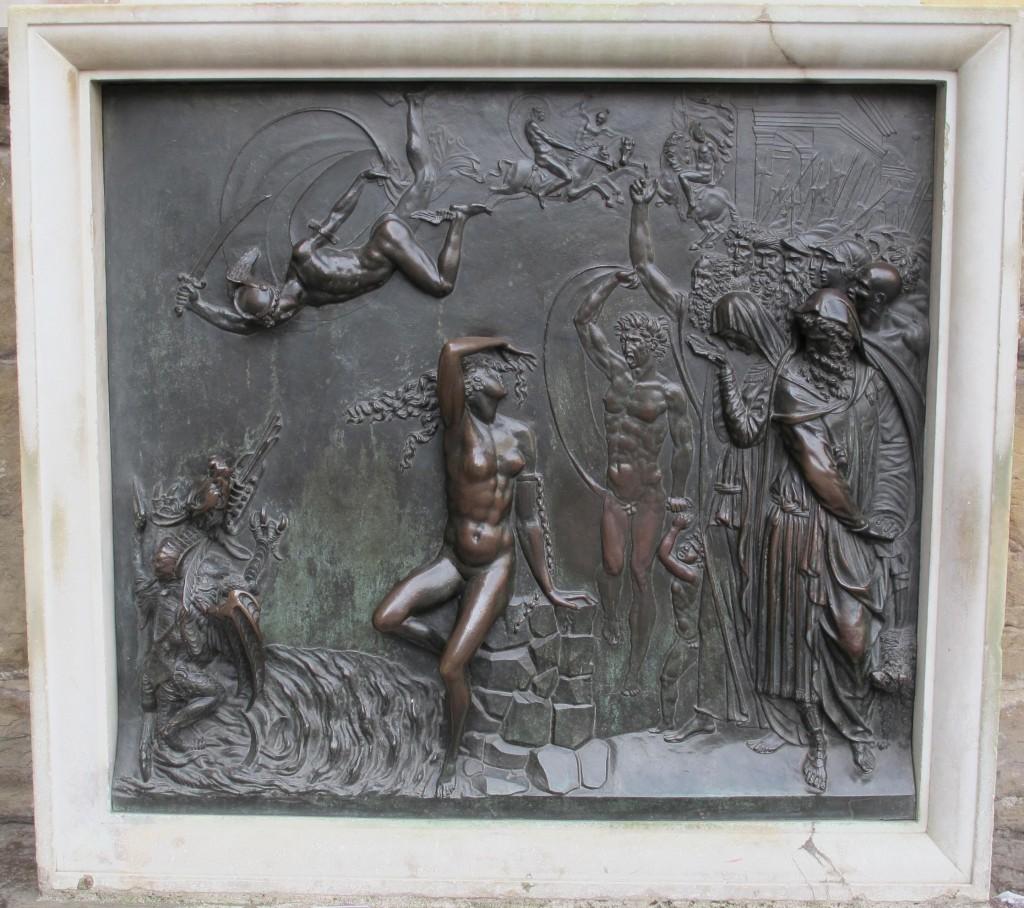 Abaixo do pedestal discriminado acima, temos ainda essa placa de bronze em relevo retratando detalhes da luta do herói enfrentando o monstro marinho Kraken, a bela princesa Danae acorrentada pelo braço esquerdo, Perseu prometendo trazer a cabeça da Medusa e seus pais, rainha Cassiopeia e o rei Celeu, pranteando o sacrifício da jovem.