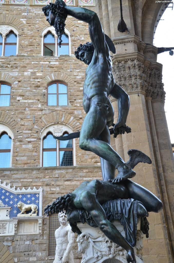 Sob o olhar de Héracles (Hércules), o jovem Perseu ostenta a cabeça da rainha das Górgonas, Medusa.
