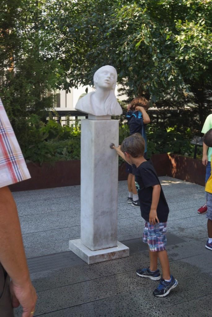 Este bebedouro é novo. Quando as pessoas bebem, parecem estar dando um beijo na mulher da escultura...