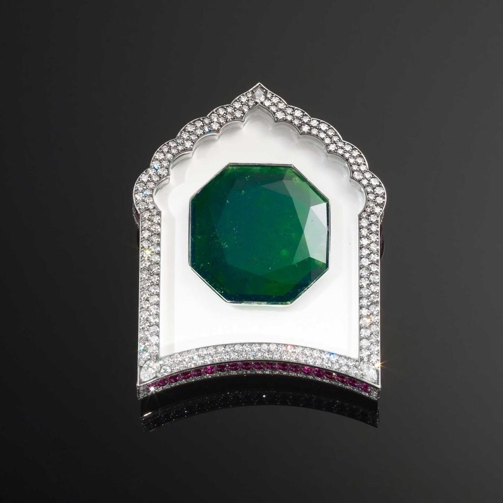 Essa é uma peça incrível. Não adoro o design, mas a cor da esmeralda ao vivo é incrível. Ela esta sobre uma pedra branca e segurada por um cristal de rocha puríssimo transparente ao redor.