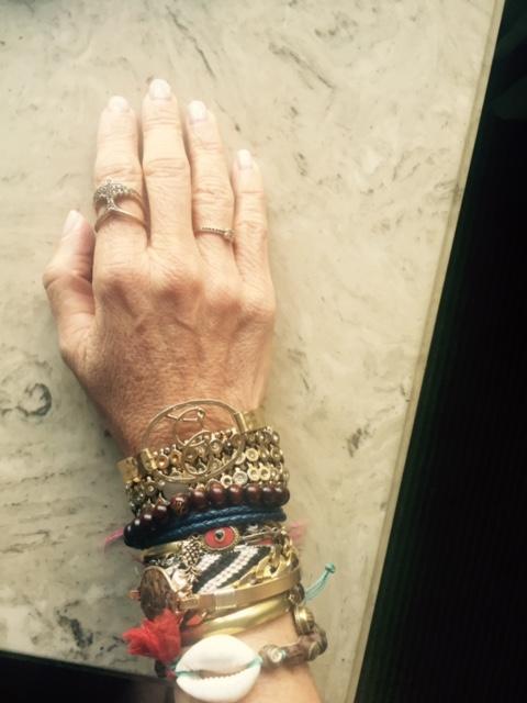 """A primeira, grossa com """"brilhantes"""" é Rose Benedetti de alguns anos atras! As de pano sao do calçadão da praia de Copacabana. A de bolinhas de madeira, presente de monje Tibetano nas ruas de Manhattan, pulseiras de metal legítimo...coral e agata da feirinha da Portobello Road, fitinha do Bomfim, letra B da Anthropology, e poraí vai! Tem umas escondidas lá que nem dá para ver! Estou VICIADA!!!! (E o anel de pássaro da coleção rock&roll da H.Stern que não tiro do dedo). Beijo+abraçao, Betina Secemski"""